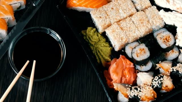Big sushi set with variety of sushi rolls, maki, nigiri, gunkan on a stylish dark background. Soy sauce and bamboo chopsticks lie nearby video