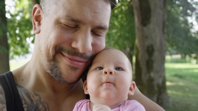vídeos de stock e filmes b-roll de close up: big tattooed father sharing gentle moments with his baby girl in park - super baby