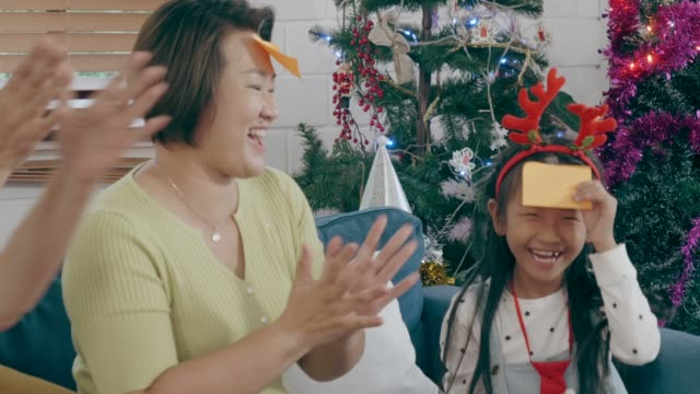 Big Thai family Playing Guessing Game at Christmas party Thailand, Bangkok, daughter, lifestyle, family, grandmother, mother, grandchild, bonding, happiness, enjoyment, leisure game, talking, guess, fun, daughter, bird, mother, grandmother, Christmas party christmas fun stock videos & royalty-free footage