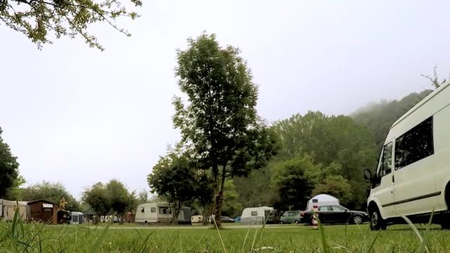 stockvideo's en b-roll-footage met grote boom in het midden van een kampeerplaats - caravan