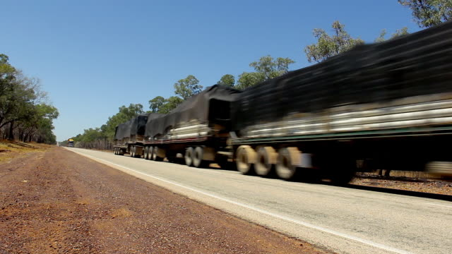 big trucks with three trailers passing by empty road in outback australia - transport truck tyres video stock e b–roll