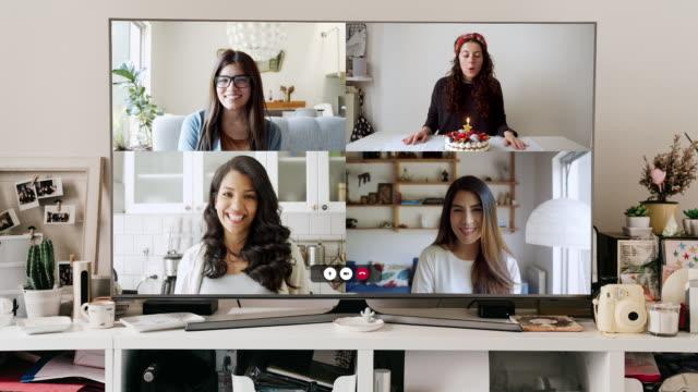 stockvideo's en b-roll-footage met grote tv-monitor met een videoconferentie gesprek op het scherm - vrienden vieren een virtuele verjaardag partij - vier personen