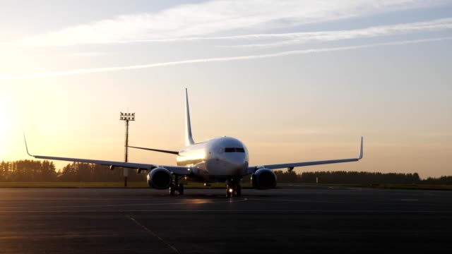 Big white plane preparing to fly starting to move on runway at sunset. Passenger jet on airstrip in airport airfield. Big white plane preparing to fly starting to move on runway at sunset, front view. Spotting hobby concept. airfield stock videos & royalty-free footage