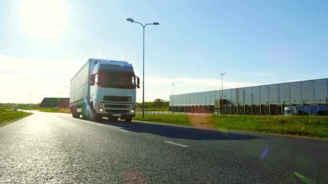 Gran blanco Semi camión con remolque de carga se mueve en el camino de vacío de área de nave Industrial con el sol brillando en el fondo. - vídeo