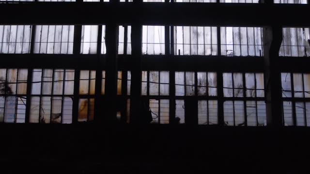 Big windows from inside of an old and abandoned warehouse Big windows from inside of an old and abandoned warehouse. Broken windows rough rusty industrial equipment. abandoned stock videos & royalty-free footage