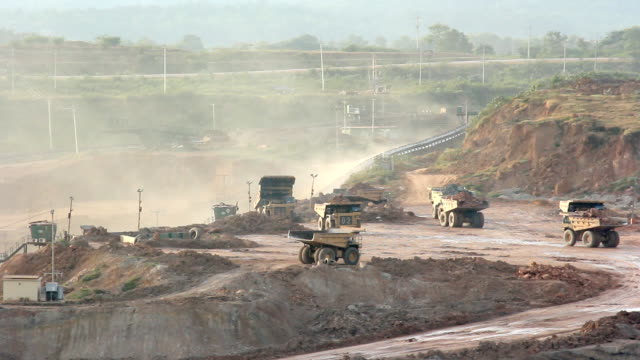 big yellow mining trucks at work in coal mine. video