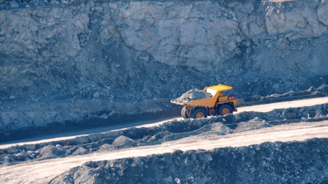 Big yellow trucks transport ore in an asbestos mineral quarry. Open pit mine. Big yellow trucks transport ore in an asbestos mineral quarry. construction vehicle stock videos & royalty-free footage