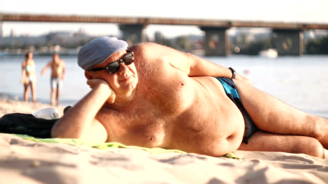 Big-bellied man is resting on the beach - stock video. Senior man resting, lying on sand at the beach.  Summertime travel vacation at the beach. Senior man body on beach In summer. Man in swimming trunks and a cap sunbathing on the beach. swimwear stock videos & royalty-free footage