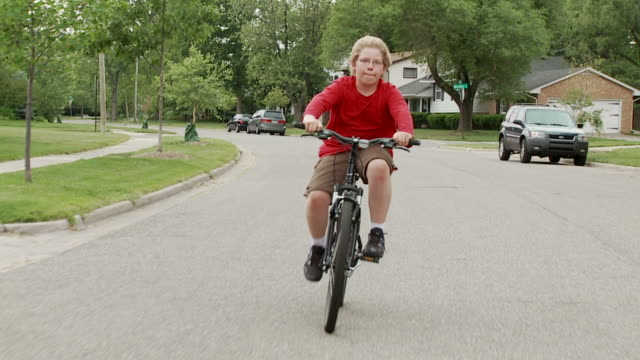 Bike Boy On Road 24_5S Boy riding a bicycle in the road through middle-class, mid-western American suburb.  Recorded from a moving vehicle with camera mounted on a gyroscopic stabilizer.  Slow-motion, recorded at 60fps.  Head-on shot with boy weaving a little across the street. one boy only stock videos & royalty-free footage