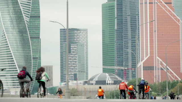 vídeos de stock e filmes b-roll de bike city events competition in background of skyscrapers, crowd of cyclists from thousands of people riding bicycles, unrecognizable people in blur, timelapse - bike emoji