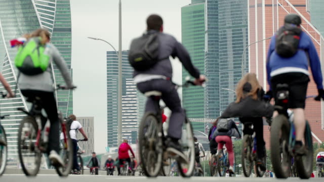 vídeos de stock e filmes b-roll de bike city events competition in background of skyscrapers, crowd of cyclists from thousands of people riding bicycles, unrecognizable people in blur - bike emoji
