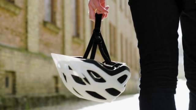 ein fahrradlieferant, der seinen helm trägt - kopfbedeckung stock-videos und b-roll-filmmaterial