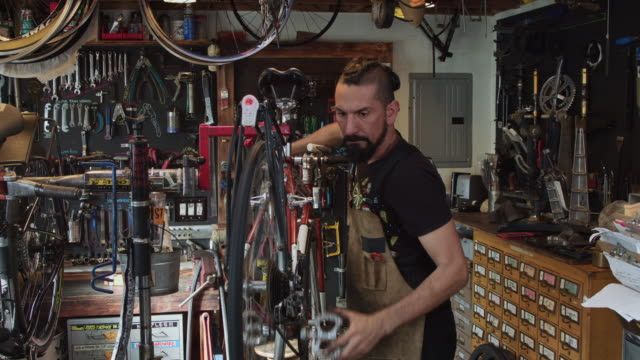 Bike Mechanic Adjusting Bicycle on Stand and Shifting Through Gears Mechanic at work in a bicycle workshop. independence stock videos & royalty-free footage