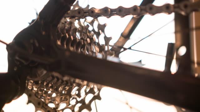 bike wheel, gear and chain in motion, illuminated by sunlight - ciclismo su strada video stock e b–roll