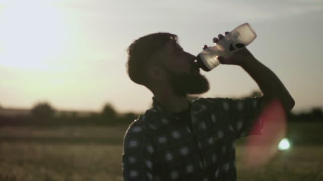 Biker trinkt Wasser dabei eine Pause bei Sonnenuntergang – Video