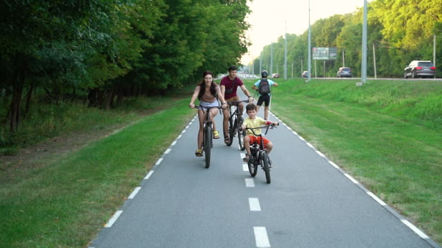Biker family riding on bicycle lane near busy city road video
