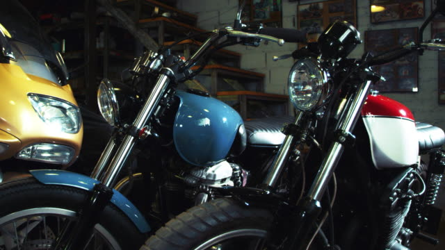 Biker garage with motorbikes. Moto service interior Biker garage with motorbikes. Close-up vintage and modern motorcycles kept in custom garage. Moto service interior. Tuning and restoration retro classic motorbikes. Old school moto technics exhibition motorcycle stock videos & royalty-free footage