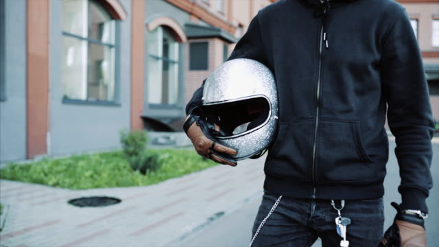 biker goes to his cool and custom motorcycle in a big city - guanto indumento sportivo protettivo video stock e b–roll
