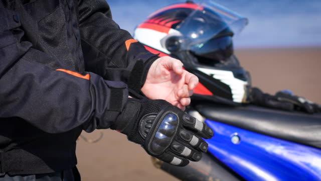 vidéos et rushes de motard dans la rue à côté de sa moto, enlève ses gants - moto sport