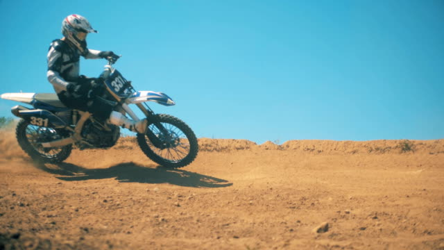 fmx biker is riding through dust with his legs up in the air. slow motion - supercross video stock e b–roll