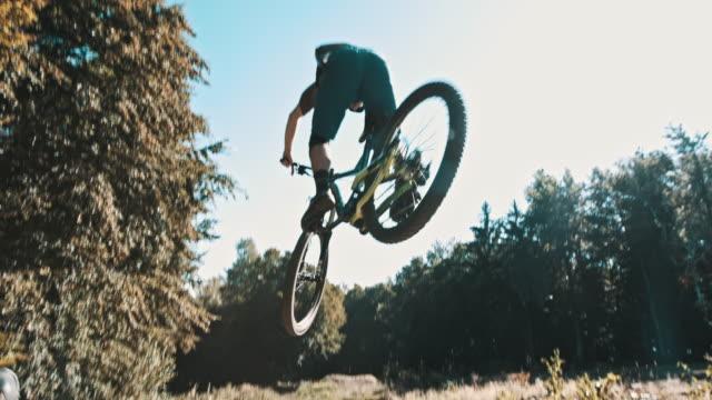 slo mo mtb biker jumping over the camera - adrenalina video stock e b–roll