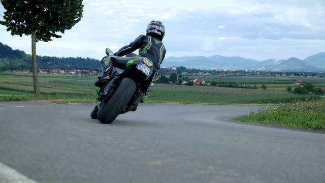 vidéos et rushes de biker faire une course et tournez à droite. - moto sport
