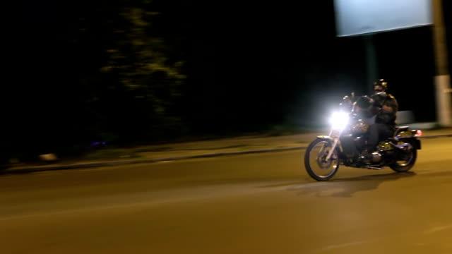 Biker on a custom motorcycle rides through the night deserted street