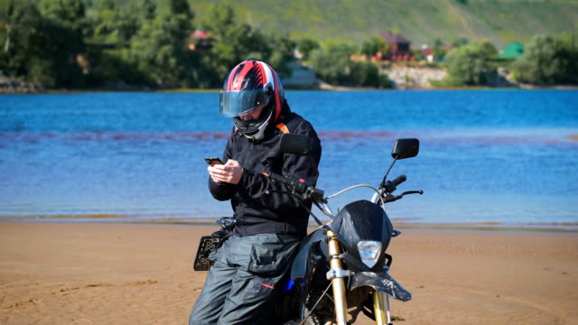 biker on the bank of the river, next to his bike, he is looking for the phone - motociclista video stock e b–roll