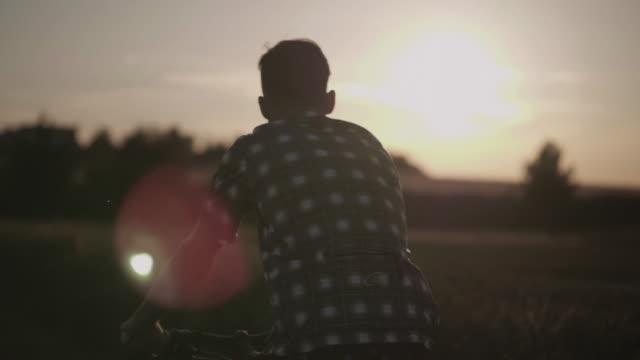 Radfahrer fährt Fahrrad neben Weizenfeld bei Sonnenuntergang – Video
