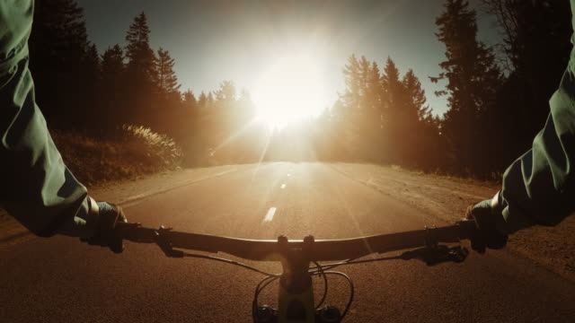 POV Biker riding his bike on a country road into sunset video