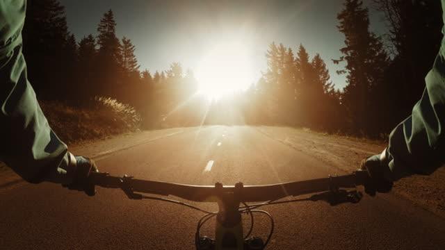 POV ciclista andando em Estrada rural ao pôr-do-sol