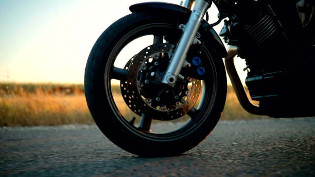 Biker riding motorcycle on an empty road at sunset Man driving motorcycle on road, motorcycle shell is custom built motorcycle stock videos & royalty-free footage