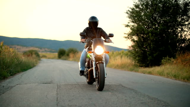 Biker riding motorcycle on an empty road at sunset