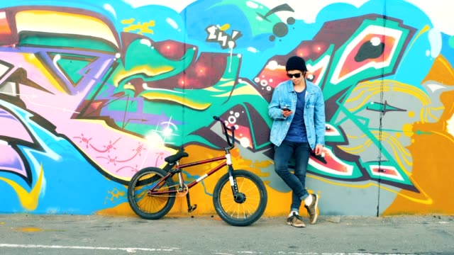 A biker stands near a wall, typing on his mobile phone. Young stylish Caucasian male teenager.