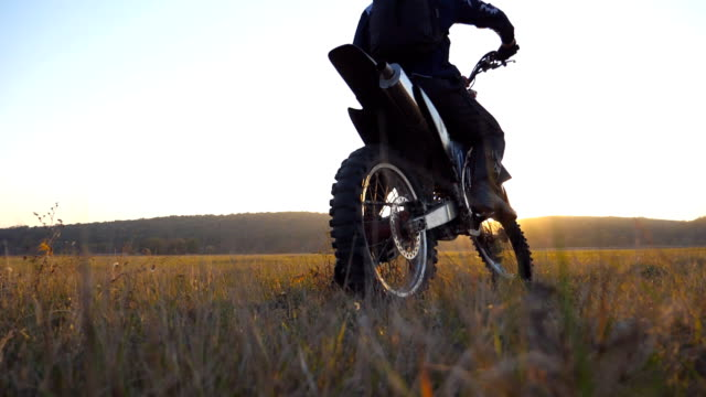 biker stopped at the field to wait for his friend. sportsman at the meadow. man enjoying ride on his motorcycle. beautiful sunset at background. slow motion close up back view - freestyle motocross video stock e b–roll