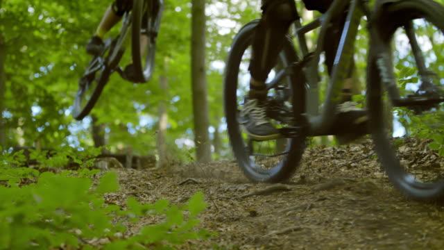 vidéos et rushes de super slo mo mtb motards sauter par-dessus une rampe sur un sentier à travers la forêt - randonnée équestre