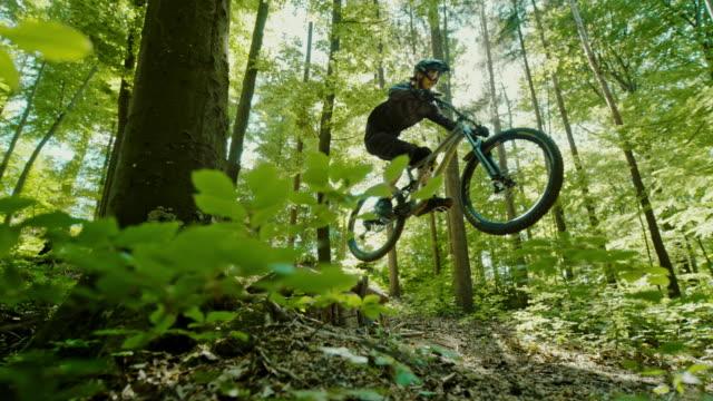 super slo mo mtb cyklister hoppa över en träramp i en solig skog - skatepark bildbanksvideor och videomaterial från bakom kulisserna