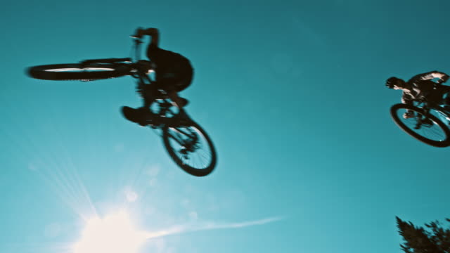 SLO MO MTB bikers jumping over the camera video