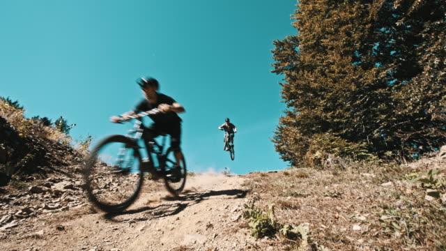 slo mo bikers riding on a downhill trail - adrenalina video stock e b–roll