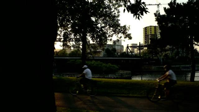 vídeos y material grabado en eventos de stock de ciclismo en la puesta de sol - estrecho