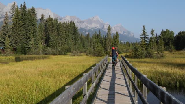 cykling par följa trä strandpromenaden över marsh, bergen - klippiga bergen bildbanksvideor och videomaterial från bakom kulisserna