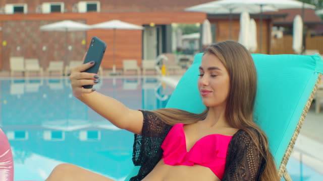 Bikini girl making photos on beach Summer, girl take selfie at pool. Tourism vacation beauty hotel tour happy holiday. Beautiful young woman in summer taking selfies on smartphone.