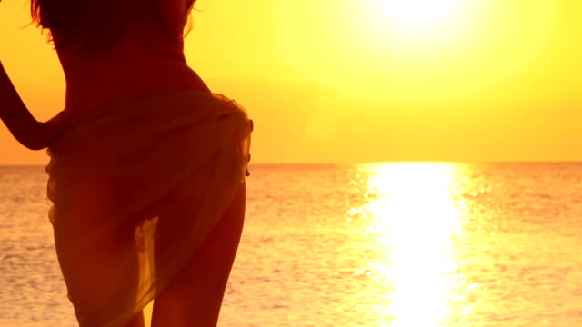 bikini model with sarong looking at sunset - beach fashion stock videos and b-roll footage