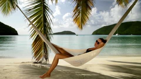 vídeos y material grabado en eventos de stock de bikini mujer dormir una siesta en las sillas reclinables en una hamaca en la playa caribeña - gente tranquila