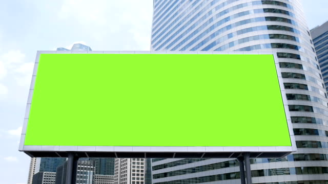 billboard with a blank green screen mock-up in front of office building in business district on a busy day, time lapse. footage for advertising background video