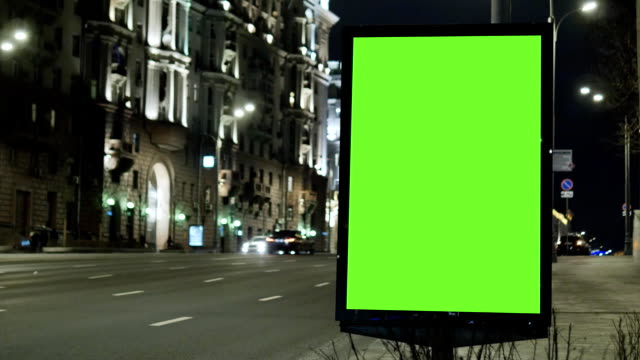 vídeos de stock e filmes b-roll de billboard with a green screen, located on a busy street. cars move in the evening. - modelo arte e artesanato