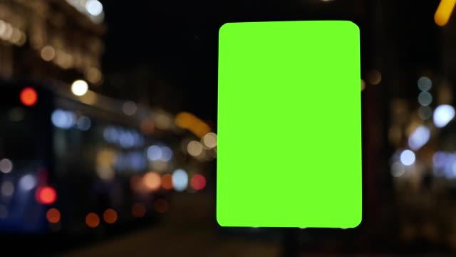 plakat mit einem green-screen, befindet sich auf einer belebten straße. autos fahren am abend. der hintergrund ist unscharf - poster stock-videos und b-roll-filmmaterial