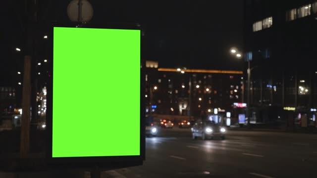 vídeos y material grabado en eventos de stock de cartelera con una pantalla verde, situada en una calle muy transitada. los coches se mueven en la noche. - póster