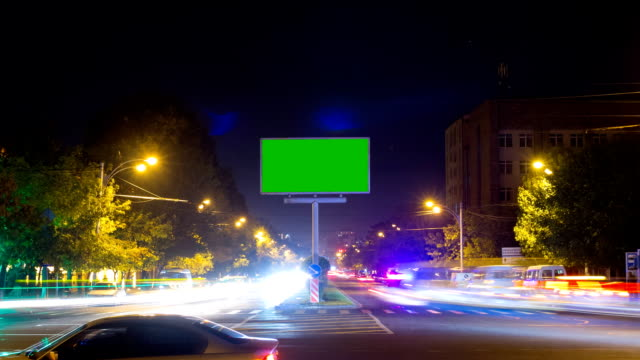 A billboard with a green screen on a background of city traffic with long exposure. Time Lapse. The camera moves away video