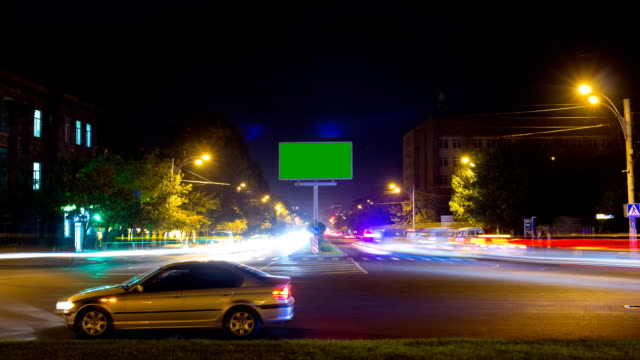 A billboard with a green screen on a background of city traffic with long exposure. Time Lapse. video